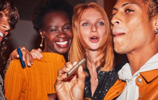Grup de oameni la o petrecere, care au IQOS în mână