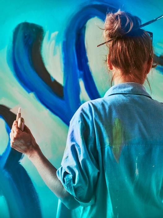 Un artist pictează în timp ce ține în mână un dispozitiv IQOS.